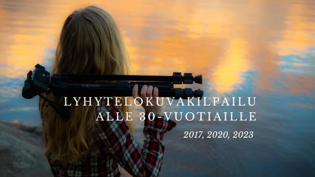 Nuori nainen kameran jalusta olkapäällään katselee rantakalliolla järven pintaan heijastuvaa laskevaa kesäaurinkoa. Nainen on hoikka ja hänellä on vaaleahkot pitkät avonaiset hiukset sekä punavalkoruudullinen paita päällään. Keskellä kuvaa on teksti: Lyhytelokuvakilpailu alle 30-vuotiaille 2017, 2020 ja 2023.