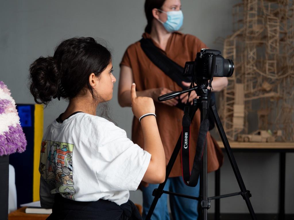 Elokuvaaja Saija Mäki-Nevala seuraa taustalla Rec-ryhmänsä keskittynyttä työskentelyä. Kuvassa näkyy hänen lisäkseen vain kuvaajatyttö, jolla on tummat pitkät hiukset sekä kamera. Mäki-Nevala käyttää maskia koronasuositusten mukaisesti.