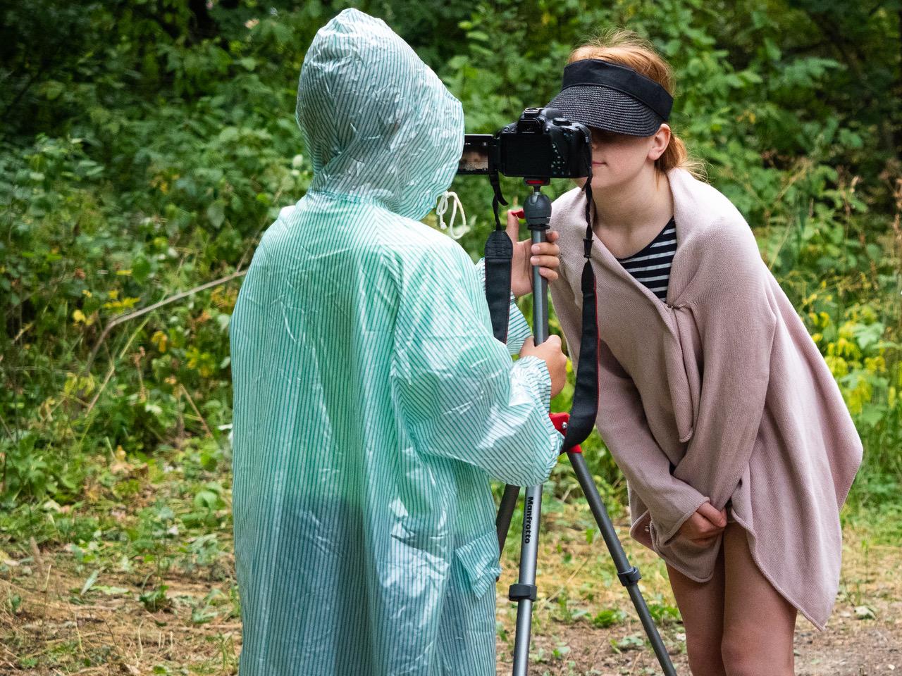 Kaksi nuorta kuvaamassa sateella. Kuvaajalla on vihreä sadeviitta päällään. Kuvattavasta, joka on kietoutunut rooliasuun, otetaan lähikuvaa.