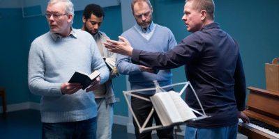 Terapiakuoron johtaja ohjeistaa kuorolaisia toinen käsi pianon koskettimilla.