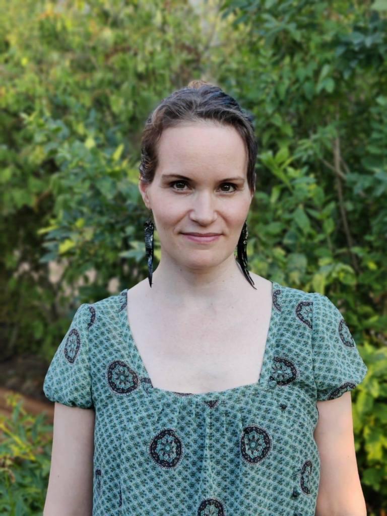 Käsikirjoittaja Petra Forstén kuvattuna  kesällä 2021. Taustalla näkyy puustoa. Tummahiuksinen Forstén on pukeutunut vihertävään kesäasusteeseen. Kuva on vain vyötäröstä ylöspäin.